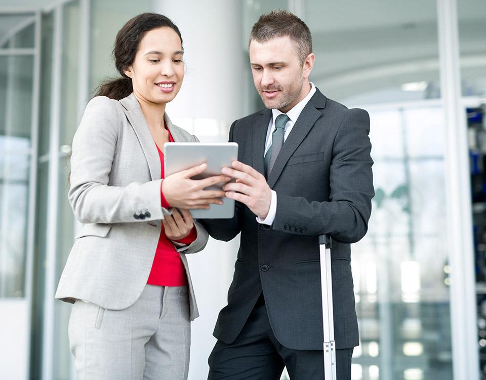 Homem e mulher observando um tablet e conversando