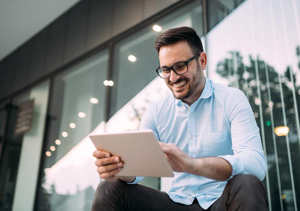 Homem sorridente lendo tablet